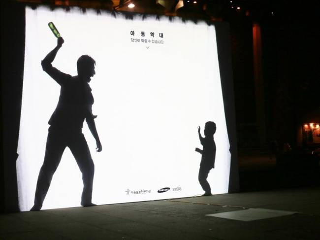 The sign displays an abusive father threatening his younger son. It is lit so that pedestrians can walk and cast their shadow on it.