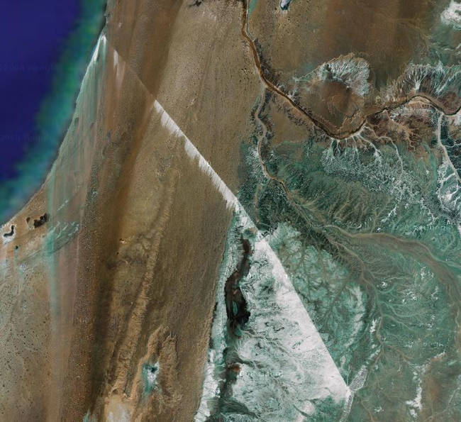 It's so long that the belt is visible as a straight line in satellite photos, and at some places, easily recognizable by a white strip of phosphates that get blown off the belt due to big Saharan winds.