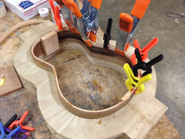 The sides of the guitar were bent and glued using a mold. The vices kept constant pressure on the wood during the process.
