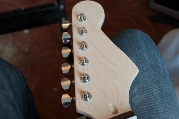 Including shaping the headstock and installing tuning pegs.